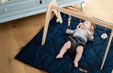 Baby liegt auf Babydecke unter Spielbogen