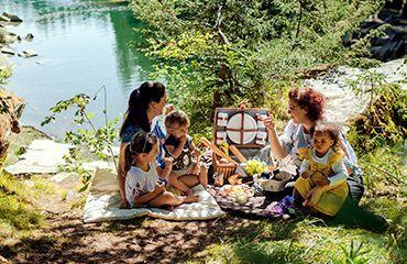 Mütter mit Kindern beim picknicken auf Picknickdecken